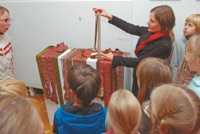 Muziejininkė Jurgita Jasevičienė rodo vaikams šio krašto juostas iš muziejaus fondų.