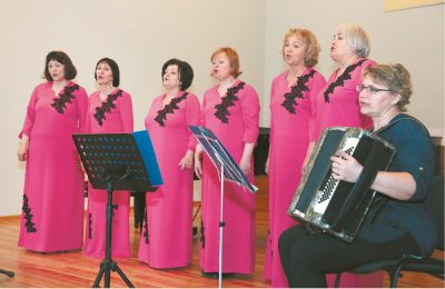 """Koncertuoja renginio šeimininkės – Marijampolės klubo """"Mozaika"""" ansamblio moterys."""