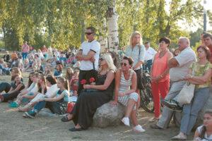 Atėję į koncertą Poezijos parke žmonės įsitaiso kaip kam patogiau...