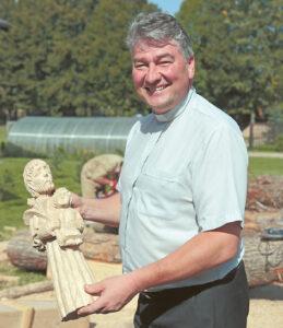 """""""Koplytstulpių parkas – tai tik didelio darbo pradžia"""", – sako klebonas A. Žukauskas. Jo rankose – Šv. Juozapo skulptūrėlė."""