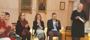 """Renginio organizatoriai ir svečiai ploja nuotaikingam """"Senapilės"""" pasveikinimui (Teresė Jurkuvienė trečia iš kairės)."""