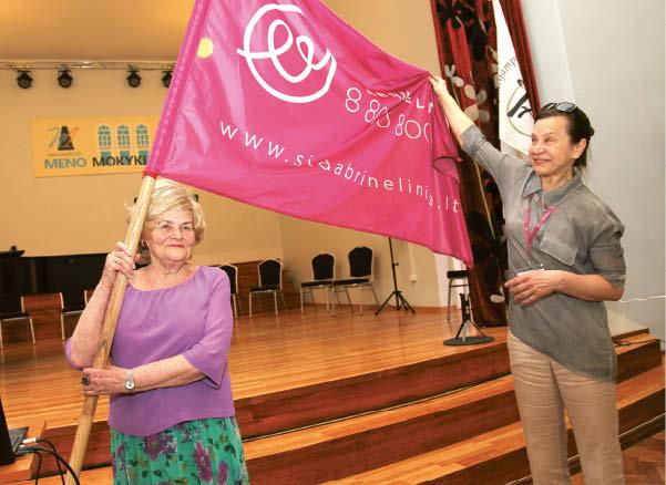 """""""Sidabrinės linijos"""" projektų vadovė Gileta Kierienė TAU direktorei Onai Sakalauskienei įteikė M. Čiuželio labdaros ir paramos fondo vėliavą. Marijampoliečiai pirmieji gavo tokią dovaną."""