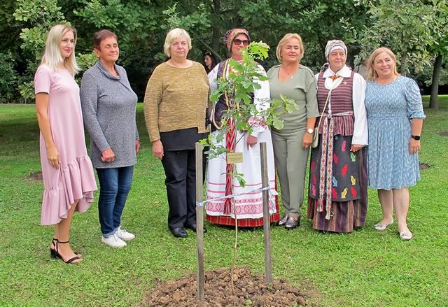 Prie šventės metu pasodinto ąžuoliuko – bendruomenių atstovai.